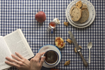 woman having breakfast, his hands and a book