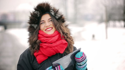 Woman holding tablet and smiling to the camera in park at winter