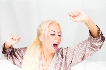 Blonde Frau gähnend im Bett