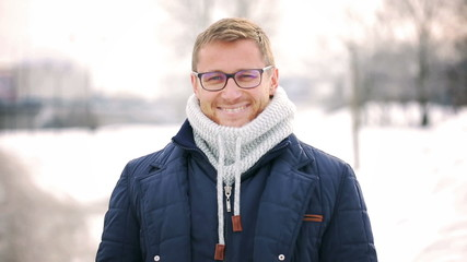 Man standing in the park at winter time and smiling to camera