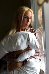 Blonde Frau stehend am Fenster