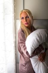 Blonde Frau stehend an der Wand