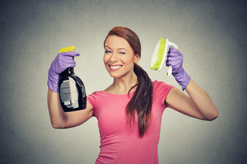 Happy woman holding brush and detergent cleaning solution bottle