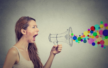 Angry young woman screaming in megaphone