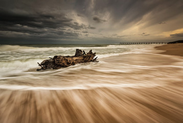 Stormy sea beach with slow shutter and waves flowing out