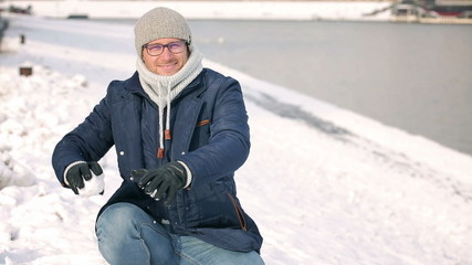 Man smiling and throwing snowballs to the camera