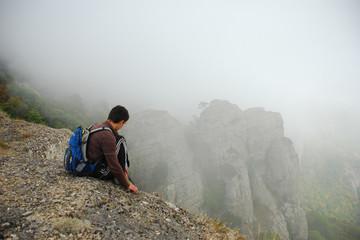 Турист, сидящий на обрыве и смотрящий на скалы в тумане