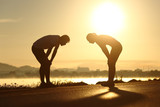 Fototapety Exhausted and tired fitness couple silhouettes at sunset
