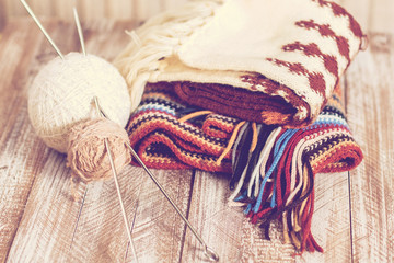 Knitting needles and yarn on rustic wooden background