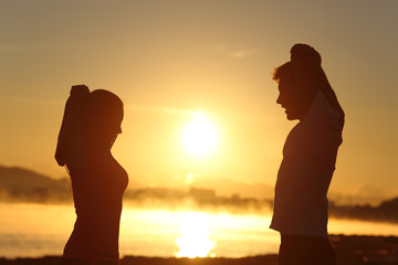 Silhouette of a fitness couple stretching at sunrise