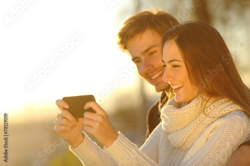 Leinwanddruck Bild Couple watching media videos in a smart phone