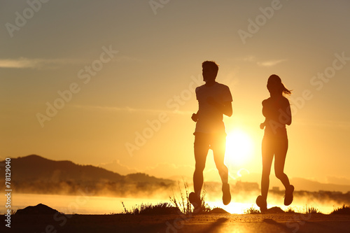 Leinwanddruck Bild Silhouette of a couple running at sunset