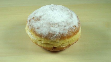 Berliner pastry with sugar powder rotating