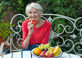 Old Woman Holding an Apple at the Garden Table.