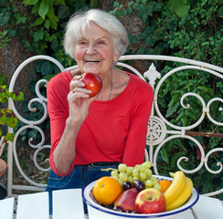 Happy Old Woman at the Garden Table with Fruits.