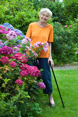 Smiling Senior Woman Standing at the Flower Garden.