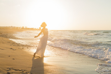 Young woman enjoys walking on a hazy beach at dusk.
