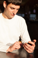 young man using a phone in coffee shop