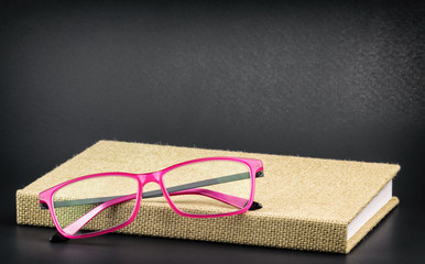 Bright pink glasses on a book, processed with grain and vignette