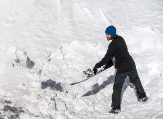 Snowboarder throws snow snowboard