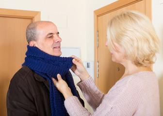 Senior woman setting scarf on man