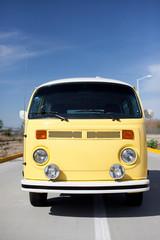 Gelber VW Bus vor blauem Himmel