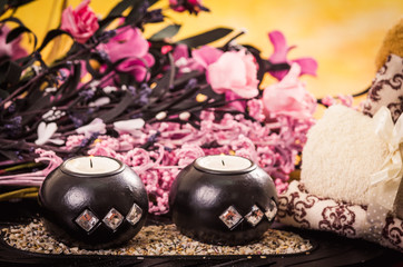 candles and towels with pink flowers spa concept