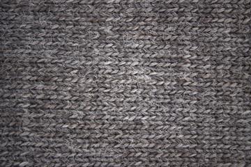 gray background of knitted woolen braids knitting stitch