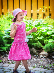 Happy Girl Outside in a Summer Dress and Hat