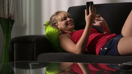 Blond Woman Relaxing On Sofa Surfing Internet With Phone