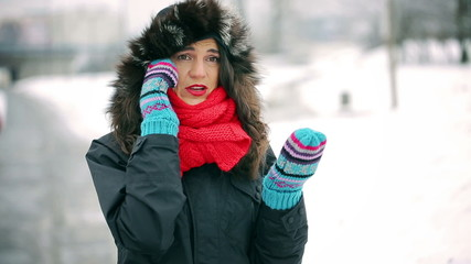 Upset woman talking on cellphone in the snowy park