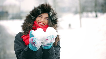 Woman showing snow to the camera and flirt in the park