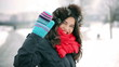 Woman walking in the snowy park and sending kiss to the camera