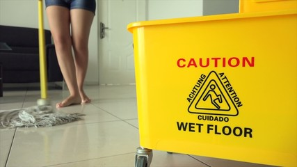 Woman Chores Cleaning Floor At Home With Yellow Bin
