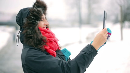 Woman recording park on tablet at winter time