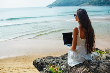 woman sitting on the rock with laptop