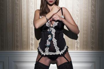 Sexy woman in underwear locking handcuffs at vintage wall