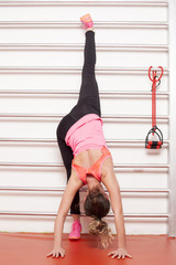 pretty woman doing exercises for stretching legs on the bars