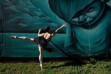 Danseuse classique devant un graffiti.