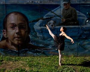 Ballerine, jambe levée, devant un graffiti.