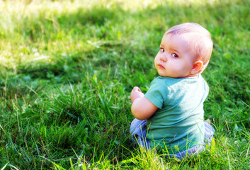 Baby Sitting on Grassy Lawn Looking Back