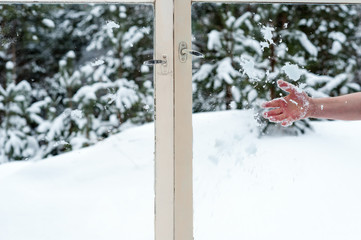 male hand throwing snow in the wooden windows