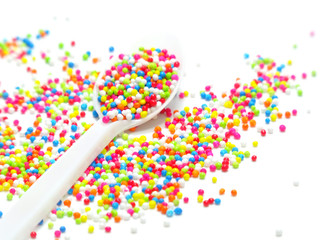 colorful sugar pearls in white spoon