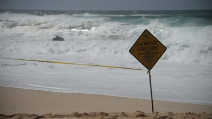 Hazardous Conditions Warning Sign at Beach with Large Surf