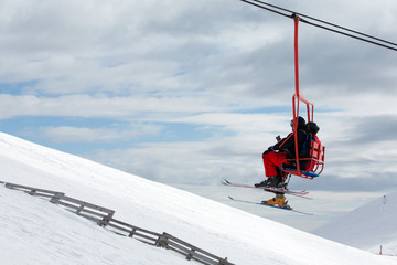 Skiers on chairlift in moutain