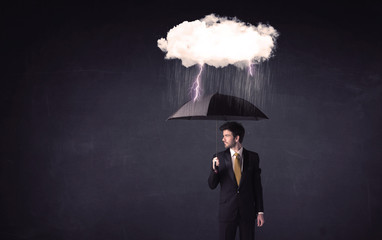 Businessman standing with umbrella and little storm cloud