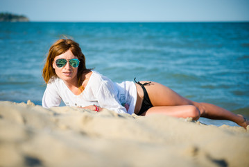 girl lying on the sand at the beach