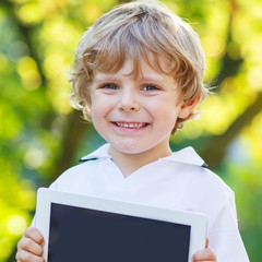 Adorable happy little kid boy holding tablet pc, outdoors
