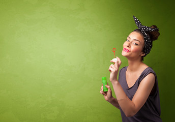 Beautiful woman blowing soap bubble on copyspace background