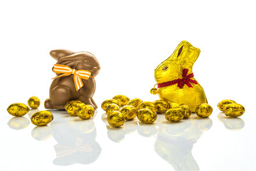 Easter chocolate bunnies and golden eggs on wooden table
